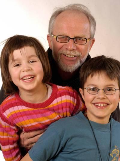 Ein älterer Herr mit Brille, grauem Haar und grauem Vollbart gemeinsam mit einem Mädchen und einem Jungen.
