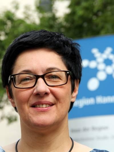 Porträt einer Frau mit Brille und kurzen, dunklen Haaren vor dem Logo der Region Hannover.