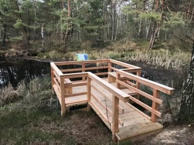 Holzsteg und Holzplattform an einem Gewässer