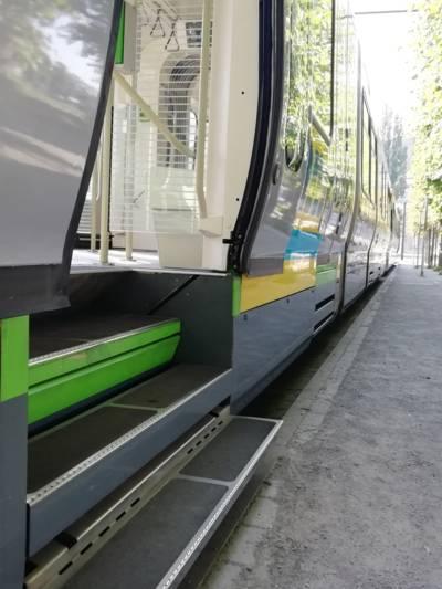 Eine Straßenbahn an einer Haltestelle mit einer geöffneten Tür und drei Stufen.