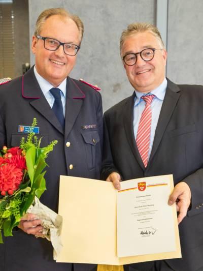 Zwei Herren mit Brille und im Anzug halten eine Urkunde, einer hat zusätzlich Blumen in der anderen Hand
