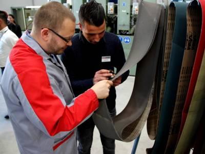 Ein junger Mann schaut sich mit einem Ausbilder Schleifpapierbänder an.