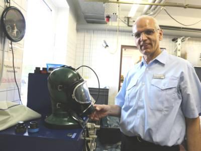 Ein Mann steht an einer Prüfeinrichtung mit Gummikopf, über den eine Atemschutzmaske gezogen ist.