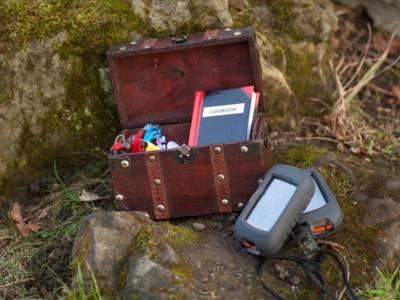 Geocache in einer Holztruhe und GPS-Empfänger
