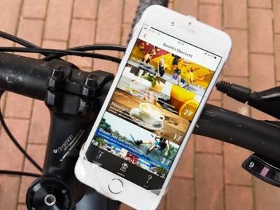 Smartphone mit laufender App an einem Fahrradlenker.