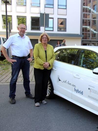 """Ein Mann (links) und eine Frau stehen neben einem weißen Auto, auf der Wagentür steht der Text """"ich bin ein hybrid""""."""