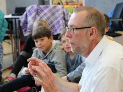Ein Mann sitzt mit mehreren Grundschulkindern auf dem Boden und führt mit ihnen ein Gespräch.