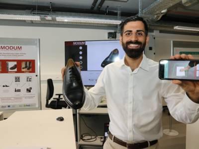 Ein Mann mit einem Schuh in der einen und einem Smartphone in der anderen Hand. Auf dem Smartphone ist ein Fuß zu sehen, der vermessen wird.