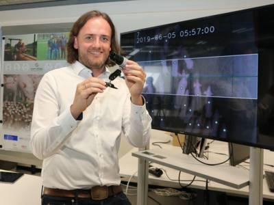 Ein Mann steht vor einem großen Bildschirm und hält einen Gegenstand in der Hand. Sieht aus wie eine Kamera.