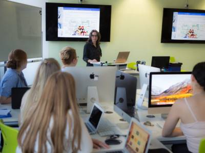 Eine Lehrerin und Schülerinnen in einem Multimedia-Raum.