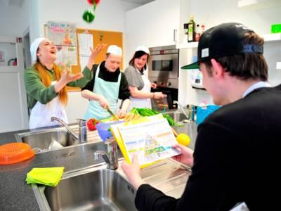 Vier Menschen arbeiten in einer Küche.