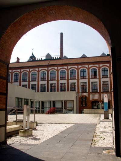 Umgebautes Fabrikgelände durch einen Torbogen betrachtet.