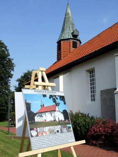 Kirchengebäude mit weißer Fassade, rotem Ziegeldach und kleinem Turm. Davor steht eine Infotafel auf einer Staffelei.