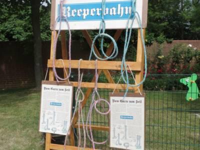An einem Holzgestell hängen Seile und Info-Tafeln.