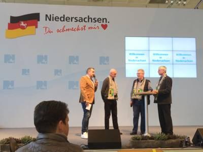 """Vier Männer stehen auf einer Bühne. Im Hintergrund steht auf einer Wand """"Niedersachsen. Du schmeckst mir. Drei Monitore zeigen außerdem jeweils """"Willkommen in Niedersachsen""""."""