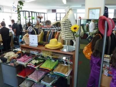 Aufnahme in einem Kaufhaus, im Vordergrund befindet sich eine Vitrine mit Kleidung. Dahinter befindet sich ein kleiderständer und Kunden an der Kasse.