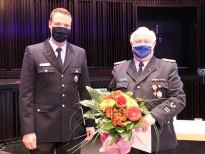Blumen und Ehrennadel zum Dank: Martin Voß (links) überreicht Eberhard Schmidt das Feuerwehrehrenzeichen am Bande.