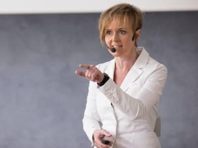 Eine Frau mit Headset hält eine Vortrag.