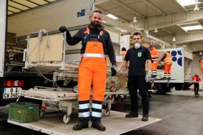 In einer Halle: zwei junge Männer auf einer LKW-Landerampe mit einem Bettgestell