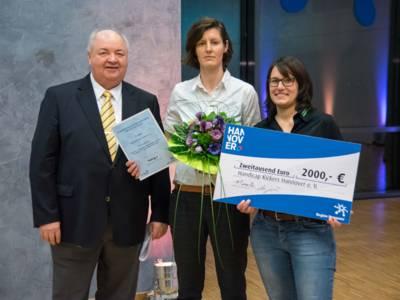 Drei Personen  mit einem symbolischen Scheck über 2.000 Euro