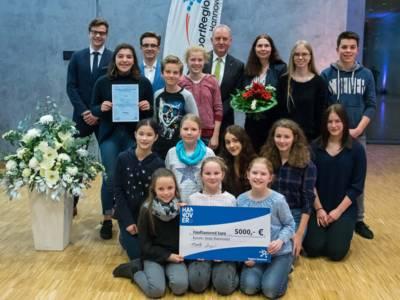 Gruppenfoto mit symbolischen Scheck über 5.000 Euro
