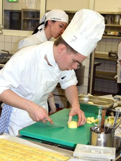 Ein Mann trägt Kochkleidung inklusive Kochmütze und arbeitet in einer Großküche mit dem Messer auf einem Schneidebrett.