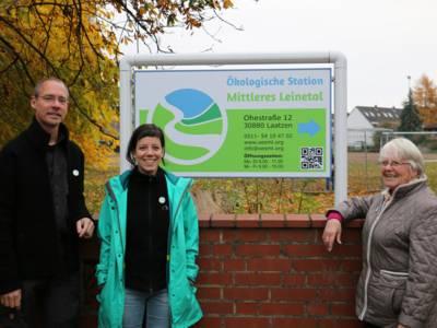 Drei Personen vor einer Mauer, im Hintergrund ein Schild