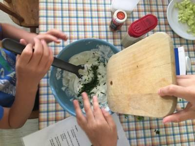 Ein Tisch mit einer Schüssel, einem Rezept, diversen Zutaten. Kinderhände, die die Zutaten in die Schüssel geben und mit einem Löffel verrühren