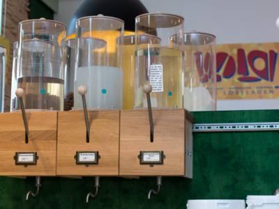 Drei Spender aus Holz und Glas für Produkte.