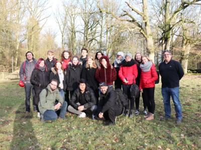 Eine Gruppe junger Menschen posiert auf einer Wiese vor Bäumen für die Kamera. Die Bäume sind noch kahl und es scheint kalt zu sein, alle sind dick eingepackt.