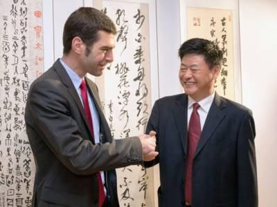 Zwei Männer reichen sich die Hände, hinter ihnen hängen weiße Papierbahnen mit chinesichen Schriftzeichen in roter und weißer Farbe.