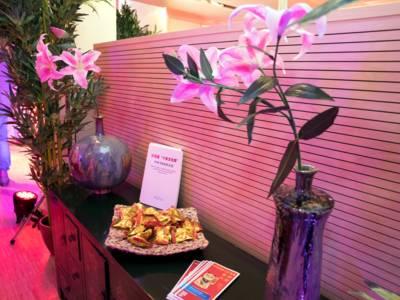 Auf einem chinesischen Schrank stehen Vasen mit Magnolienblüten, außerdem liegen Glückskekse und Faltblätter zum Mitnehmen aus.