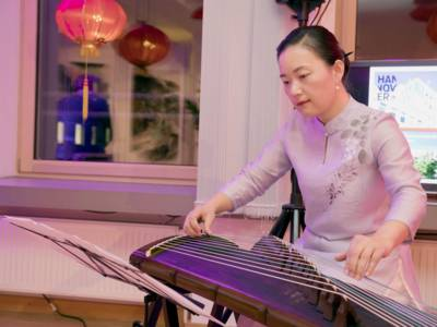 Eine Frau spielt auf einer chinesischen Wölbbrett-Zither.