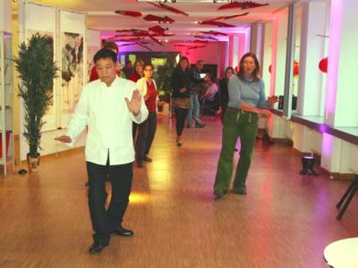Ein Mann macht Tai Chi, hinter ihm machen einige Menschen seine Bewegungen nach.