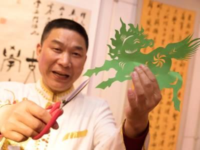 Ein Mann bearbeitet grünes Papier mit einer Schere, es entsteht ein Pferd.