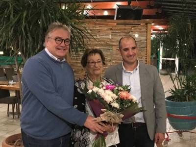 Zwei Männer umrahmen eine ältere Dame, die einen großen Blumenstrauß in den Händen hält