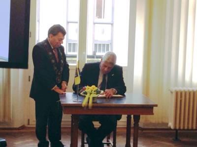 Moti Dotan sitzt an einem Tisch und schreibt, daneben steht Rolf-Axel Eberhardt, der seine Bürgermeisterkette trägt.