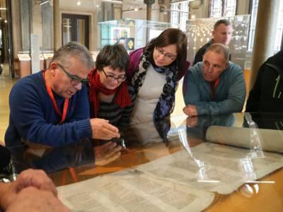 Vier Personen schauen sich Ausstellungsstücke in der neuen jüdischen Synagoge in Berlin an.