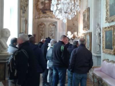 Delegation in Schloss Sanssouci, von der Decke hängt ein Kronleuchter.