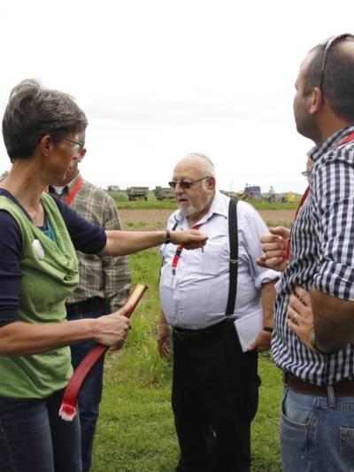Eine Frau reicht Rhabarber, drei Männer und eine weitere Frau stehen mit ihr an einem Feld.