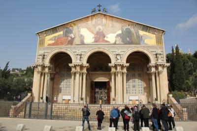 Eine Gruppe von Personen vor einer Kirche, deren Eingangsportal mit Säulen und einem Gemälde gestaltet ist.