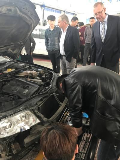 Berufsschüler arbeiten an der Front eines Autos, Delegationsteilnehmer beobachten sie dabei.