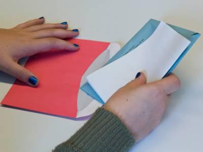 Eine Person, die ihre Wahlunterlagen in den roten Briefwahlumschlag.