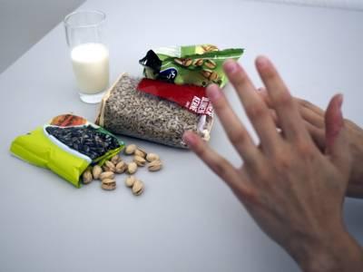 Ein Glas Milch, eine Packung Kürbiskerne, eine Packung Sonnenblumenkerne, eine Packung Pistazien und einzelne Pistazien auf befinden sichnauf einem Tisch. Über den Lebensmitteln sind zwei Hände zu sehen, mit denen eine ablehnende Haltung gezeigt wird.