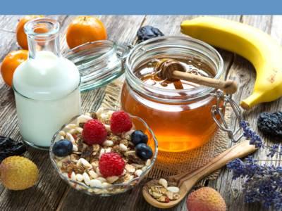 Milch, Mandarinen, Litschi, getrockete Pflaumen, Banane, Honig, Himbeeren, Blaubeeren und eine Glasschale mit einer Basismischung Müsli