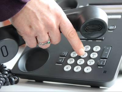 Graues Telefon, eine Hand, die den Hörer hält und gleichzeitig am Wählen einer Nummer ist