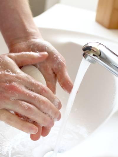Eine Person seift sich mit einem Seifenstück neben fließendem Wasser die Hände ein.