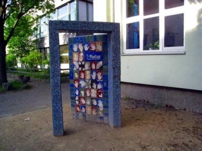 Skulptur vor dem Kulturtreff Plantage. Symbolisch ein Türrahmen mit einer geöffneten Tür. Auf der Tür sind viele Hände auf verschieden farbigen Mosaiken verteilt.
