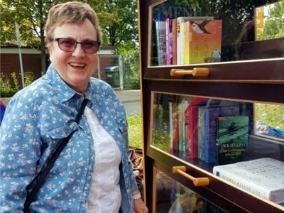 Eine Bürgerin stellt Bücher in den offenen Bücherschrank.