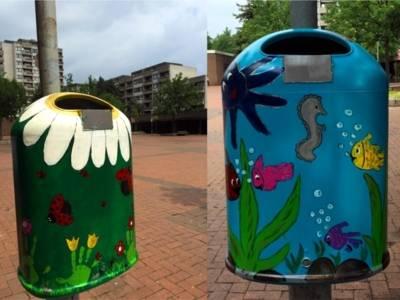 Auf dem Bild sind zwei bunt bemalte Mülleimer zu sehen. Der linke Mülleimer sieht aus wie eine Blumenwiese mit Marienkäfern und der rechte Mülleimer sieht aus wie eine Unterwasserwelt mit Fischen, Seepferdchen und Tintenfisch.